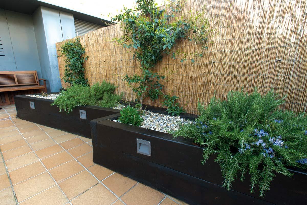 Traviesas de madera y c sped artificial en unifamiliar for Jardineras con bloques de hormigon
