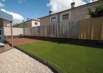 Extenso jardín con césped artificial, tarima, áridos…