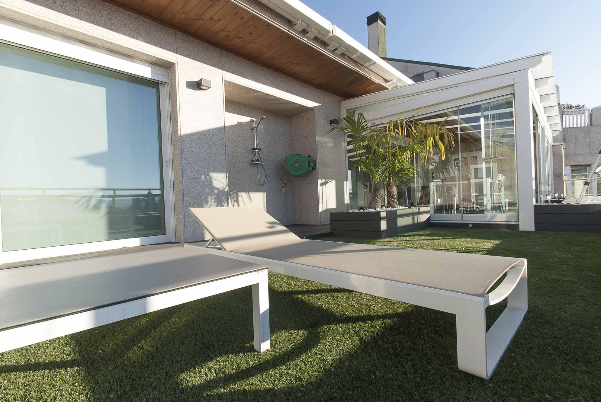 Césped artificial en terraza y porche de madera y cristal