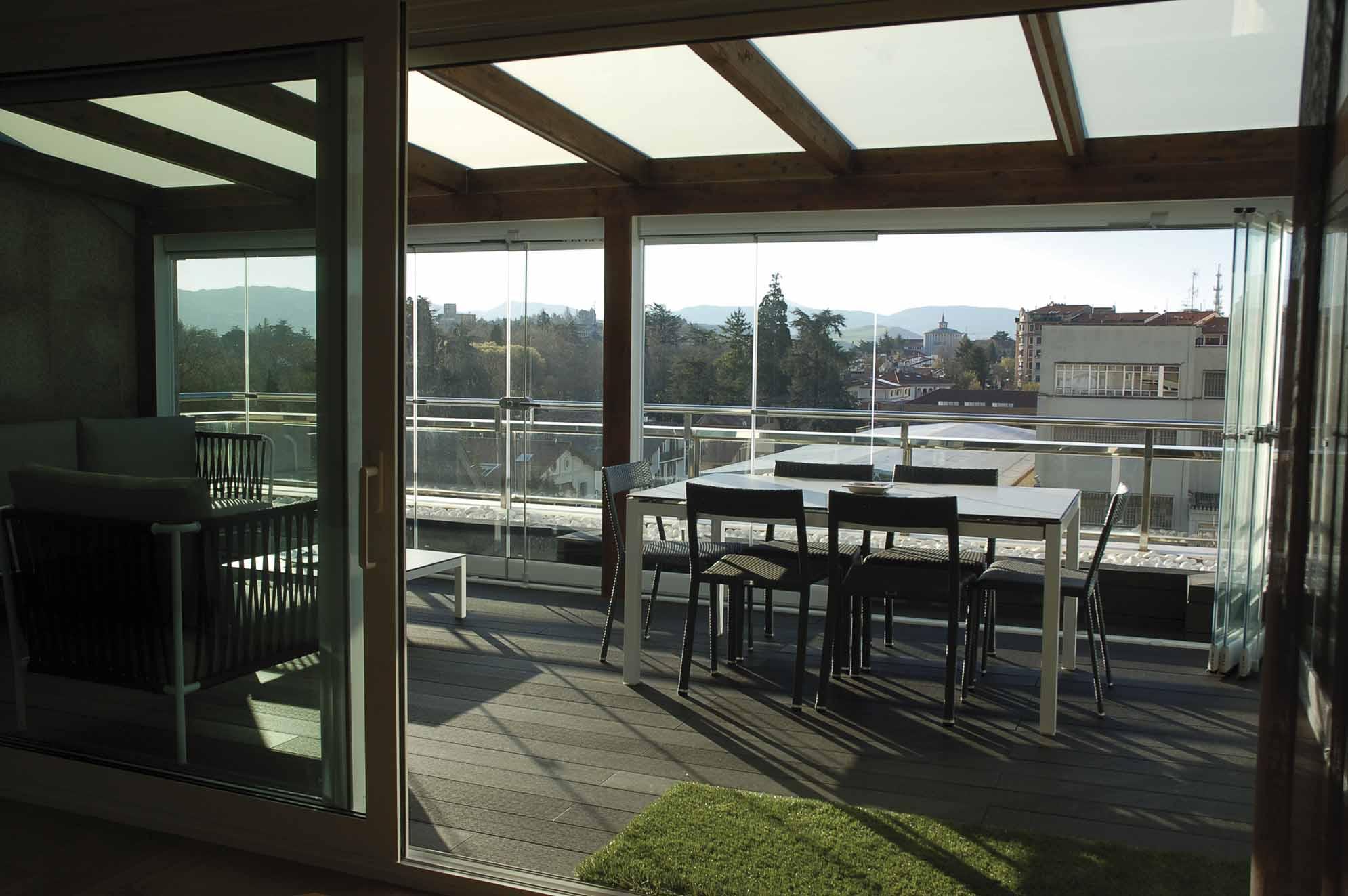 Interior del porche del ático con las cortinas de cristal abiertas