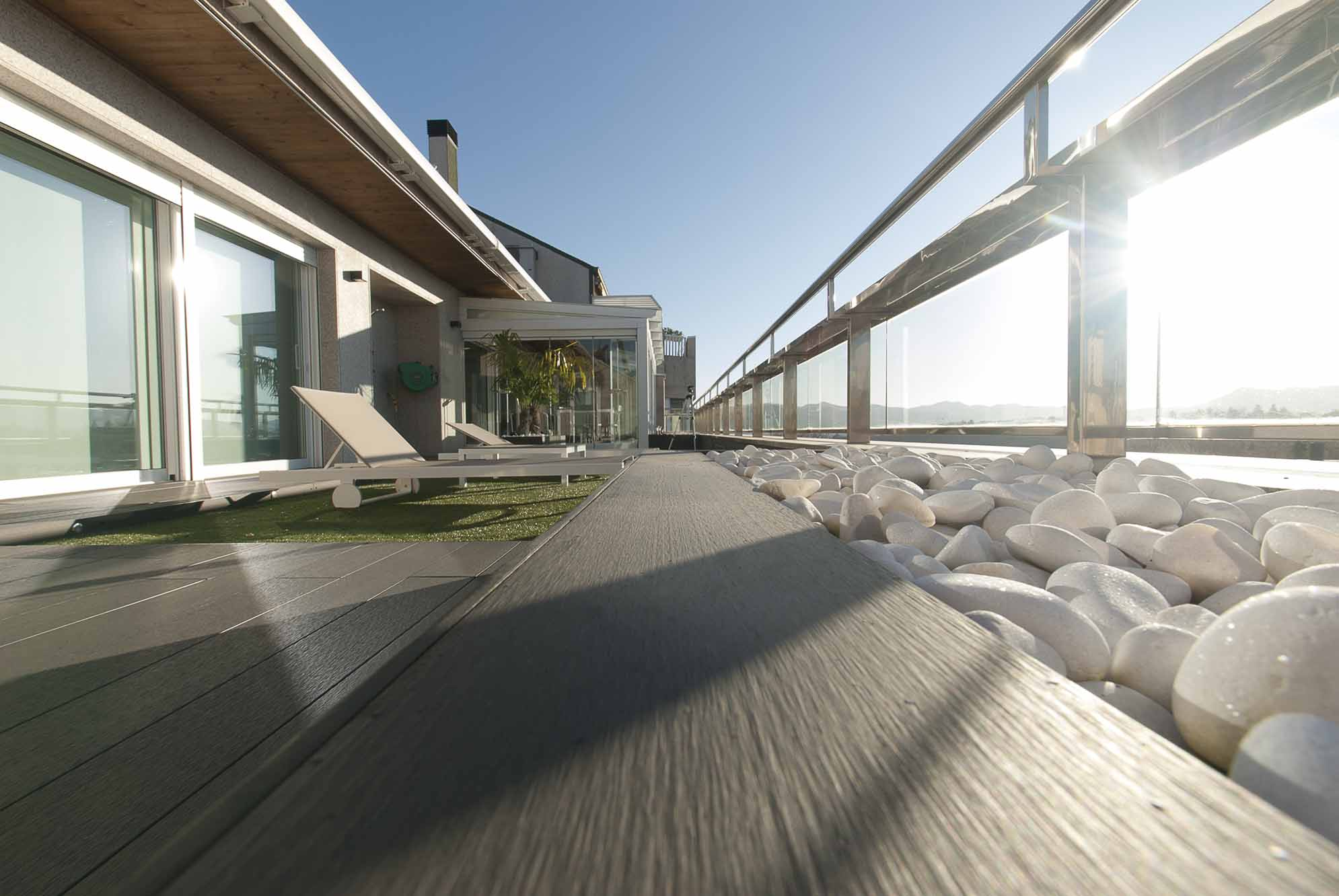 Porche de cristal y tarima de exteior en la terraza de un ático