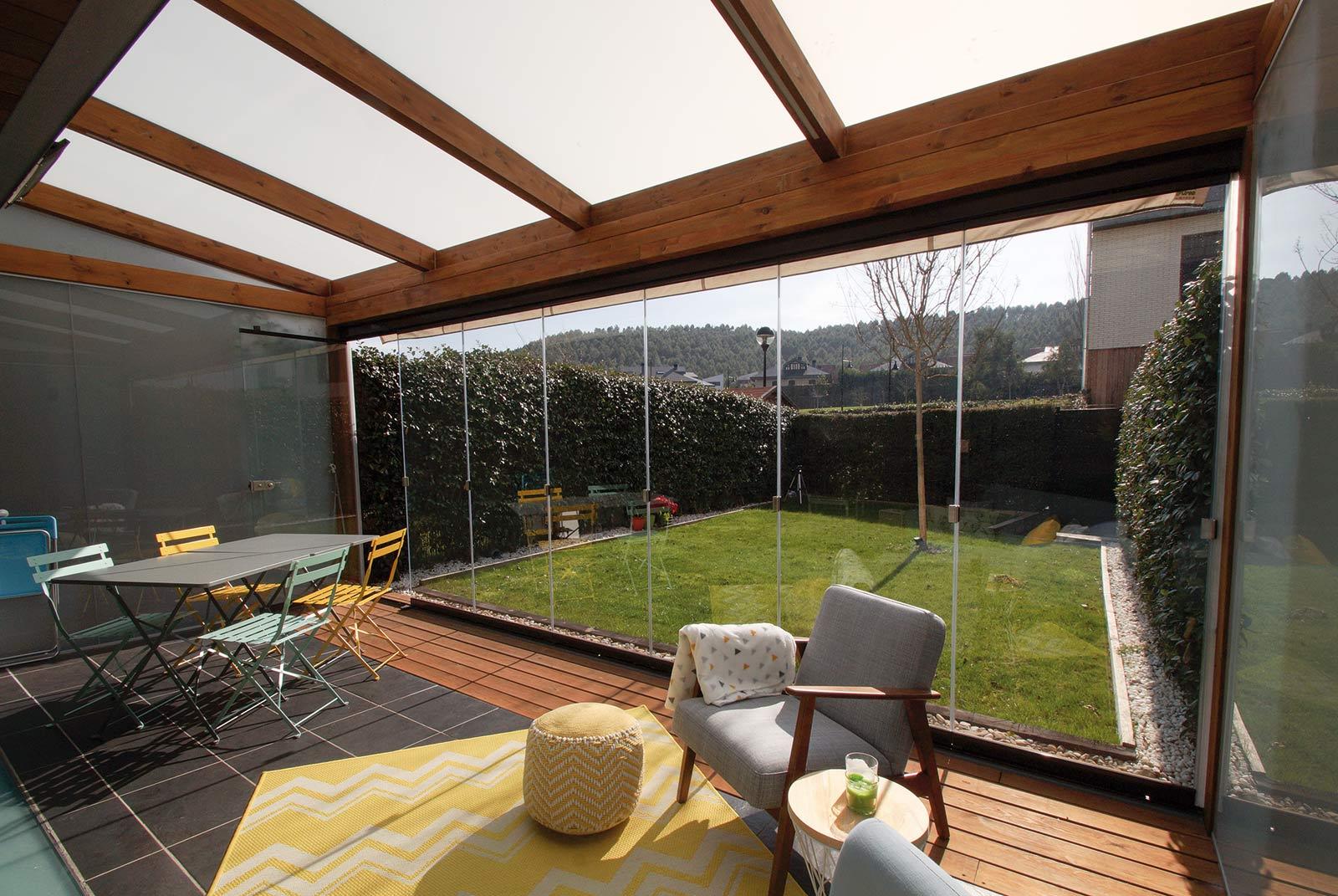 Porche de madera de estilo moderno con cortinas de cristal en jardín