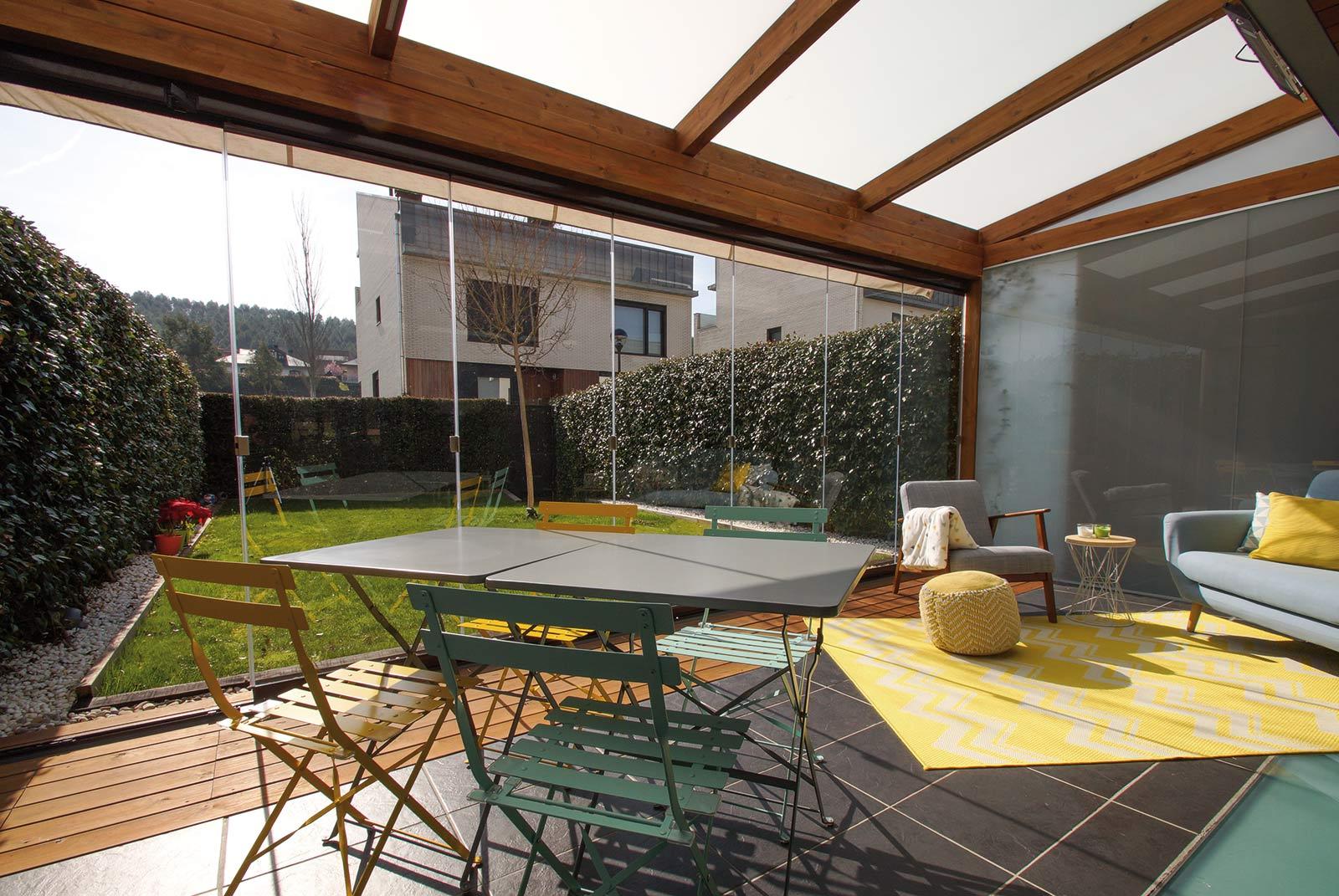 Vista interior porche de madera de estilo moderno con cortinas de cristal en jardín unifamiliar