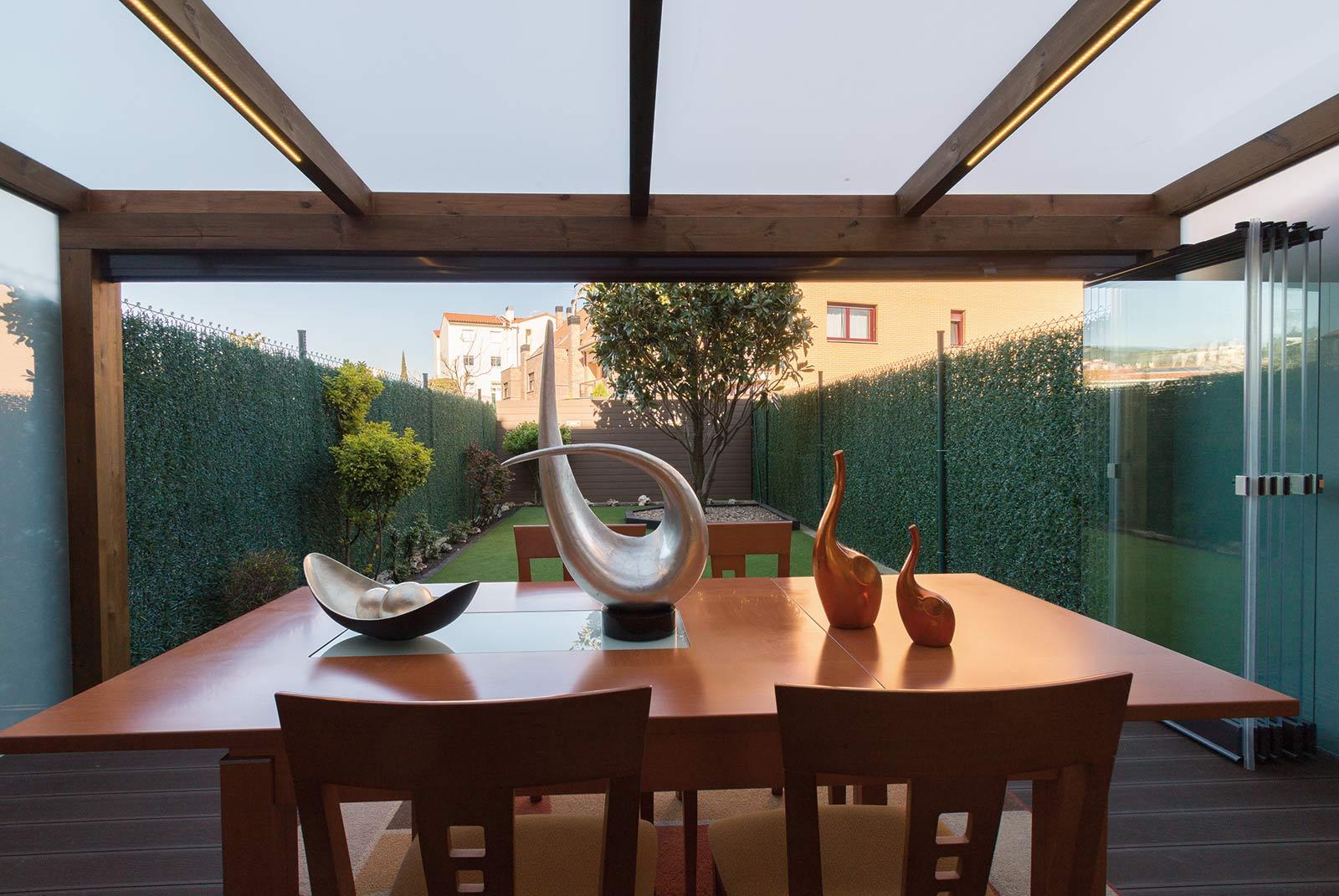 Porche de madera y cristal en jardín de bajo de mantenimiento