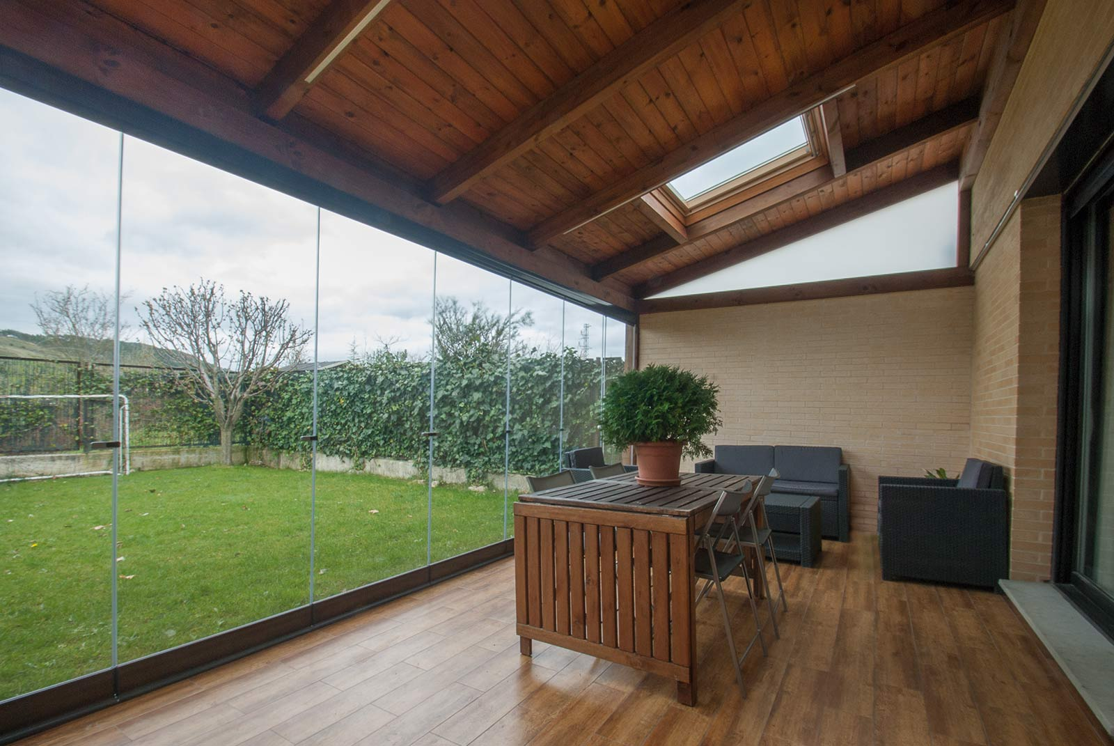 porche acristalado con techo de madera teja y velux