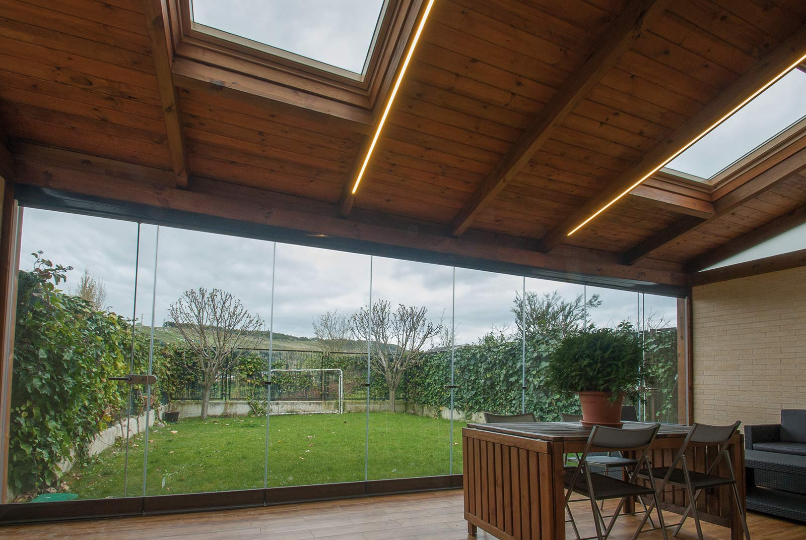 Porche acristalado con techo de madera teja y velux for Porche jardin madera