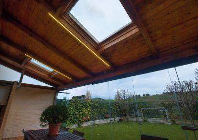 Porche acristalado con techo de madera, teja y velux