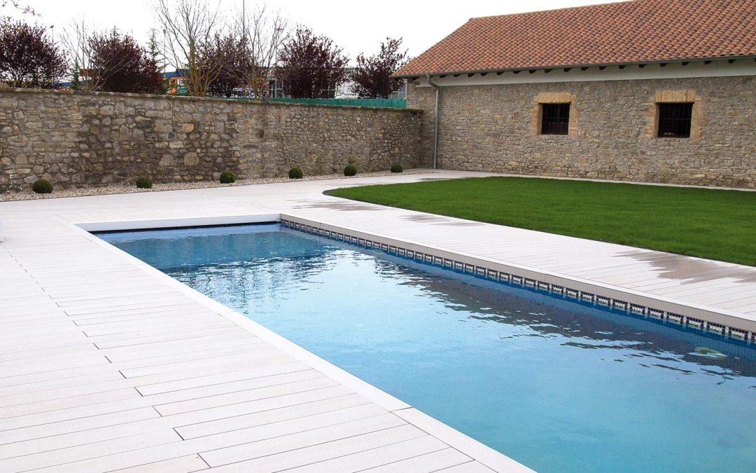 Piscina con tarima exterior y diseño de jardín