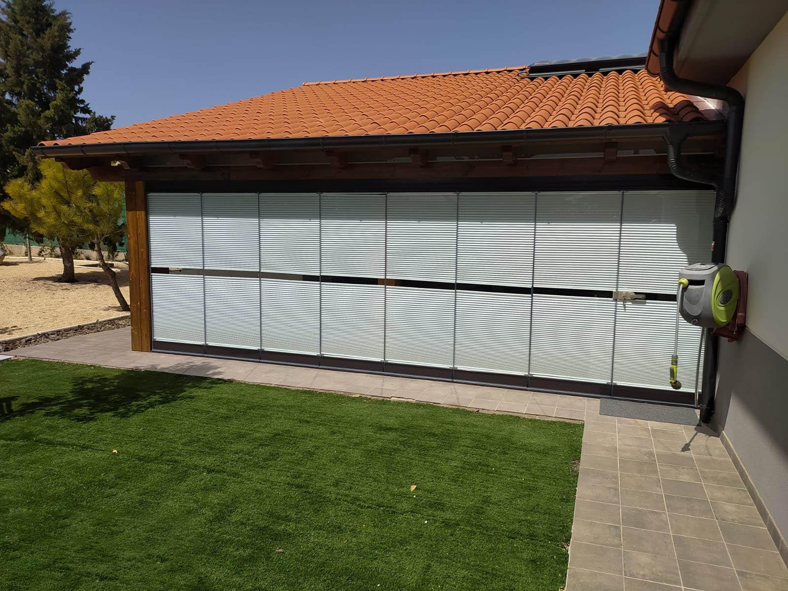 Cortinas de cristal con toldo en cubierta de porche de obra