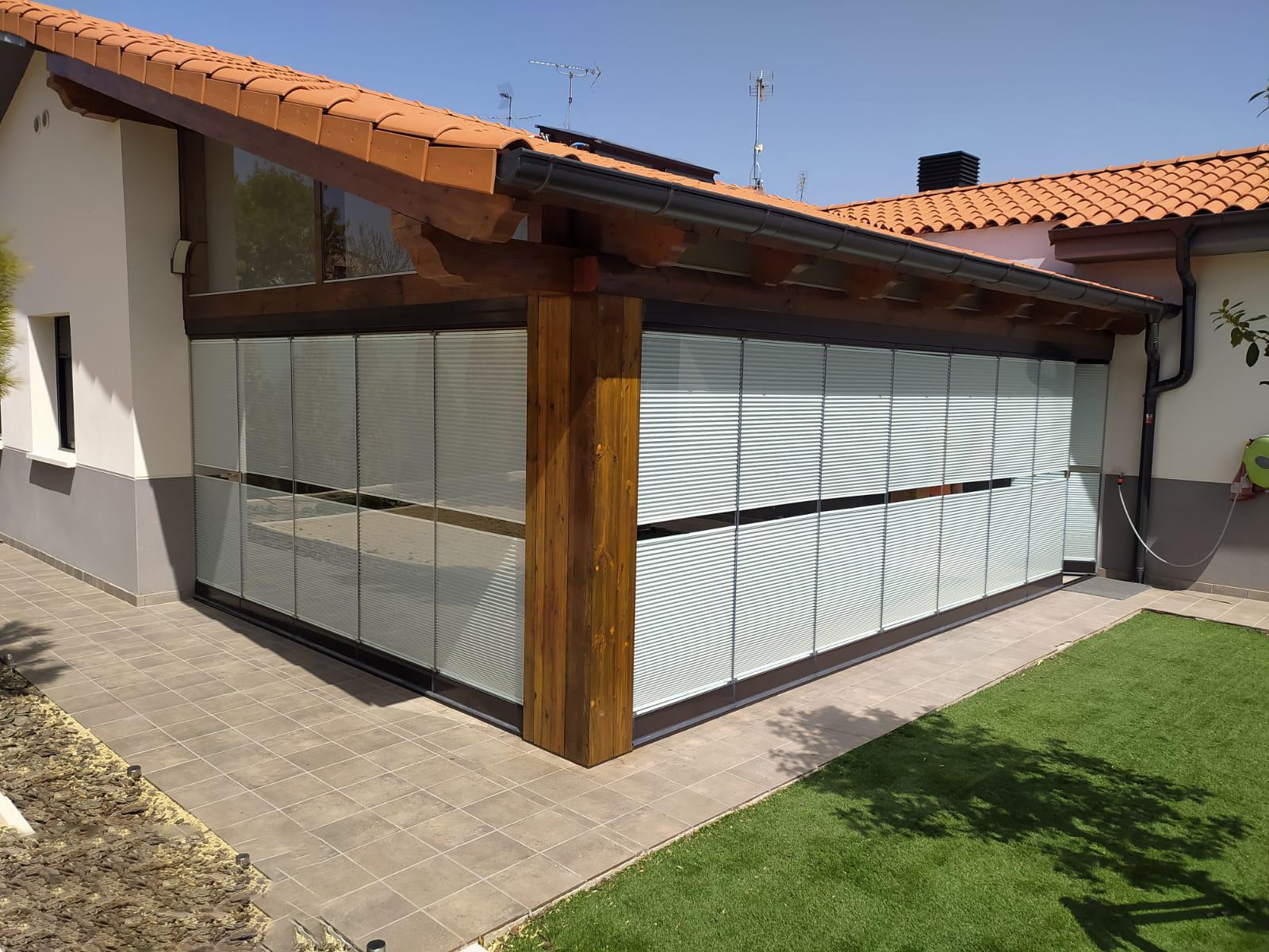 Cortinas de cristal cerrada y con stores en cubierta de porche de obra