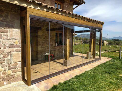 Cortina de cristal en un porche de una casa de piedra