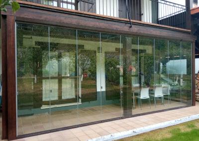 Cortina de cristal en porche de madera preinstalado
